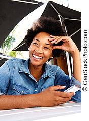 Cool young african woman smiling and holding cell phone