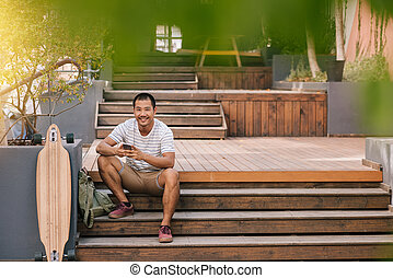 Cool young Asian man sitting outside using a tablet