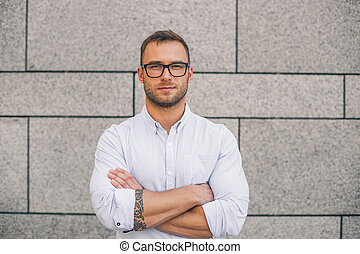 Cool young bearded hipster man wearing shirt, keeping arms crossed