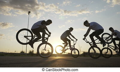 Cool young bikers team doing freestyle front wheelie trick...
