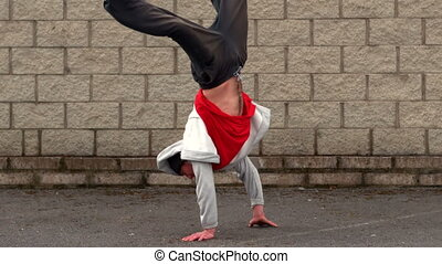 Cool young break dancer doing a handstand in slow motion