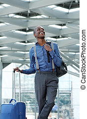 cool young businessman smiling at station with luggage