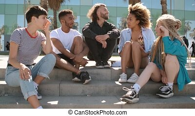Cool young diverse friends chilling on street - Happy...