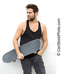 Cool young guy holding skate board