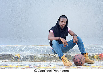 Cool young guy sitting on sidewalk with basketball