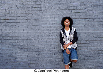 Cool young man with afro leaning against wall