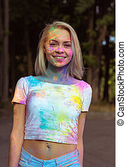 Cool young woman in white t shirt and jeans shorts covered with colorful Holi powder