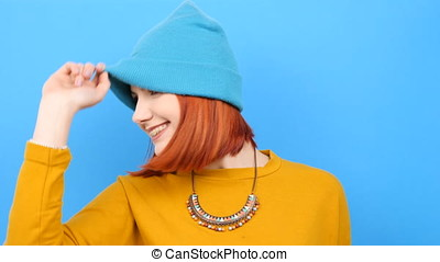 Cool young woman wearing a blue hat and playing with it