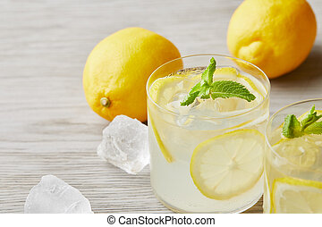 cooled lemonade glasses with ripe lemons on wooden surface