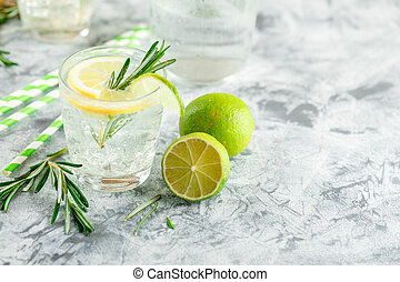 Alcoholic drink with lemon and rosemain in glasses on a light table