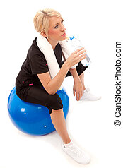 a female sat on a blue gym ball drinking a bottle of water