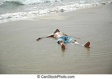 Young man on beach cooling down on wet sand