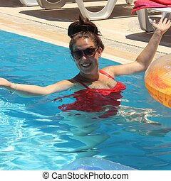 Cooling off in the swimming pool - A young english woman...