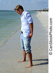 Cooling Off - Man with rolled jeans on beach