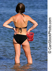 The rear view of a woman paddling in the sea and wearing a black bikini.
