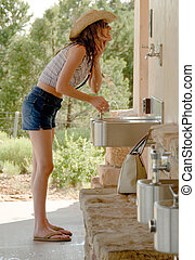 Cooling off - woman using a drinking fountain to cool off...