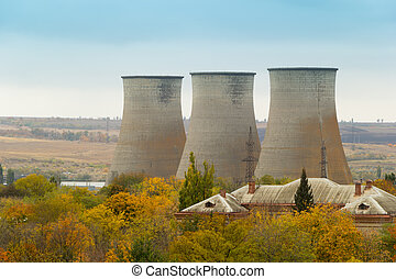Cooling towers of a power plant. Residential buildings in the foreground. Thermoelectric plant. Overcast autumn day
