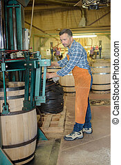 cooper making wooden wine barrels in workshop