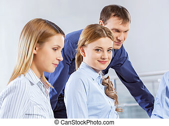 Cooperate for productive work - Three co-workers discussing...