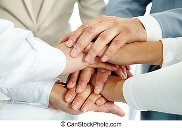 Cooperation - Image of businesspeople hands on top of each...