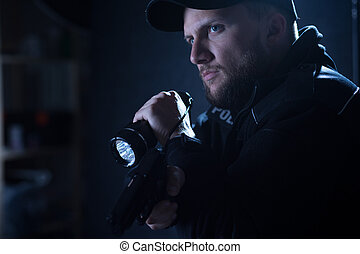 Portrait of a handsome, serious cop pointing pistol