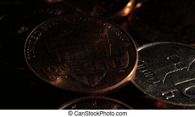 Copper coin lies near silver coins in a dark room. Close up