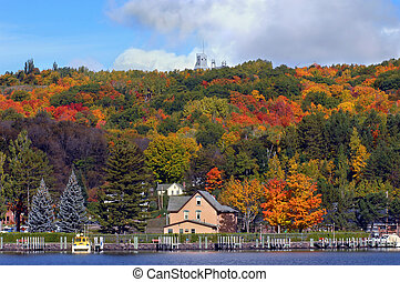 Scenic view includes Hancock, Michigan and piers with Quincy Copper Mine on hilltop. Fall foliage colors scene.