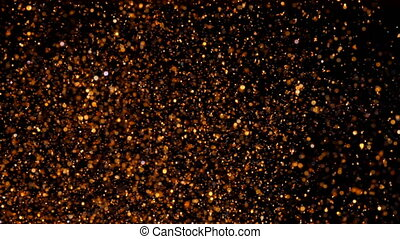 Copper particles move chaotically under water. Golden...