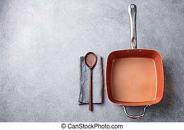 Copper saucepan on grey stone background. Copy space. Top view
