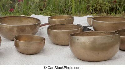 Copper singing bowls in the foreground, green grass in the background. Sound healing, meditation. High quality 4k footage
