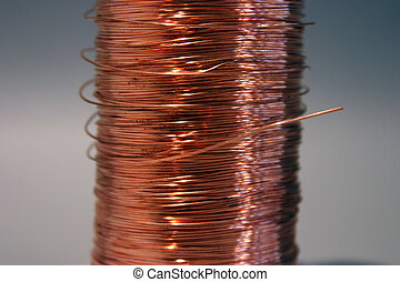 copper wire rolled up on a spool sits on a gray background with great shadows and keylighting