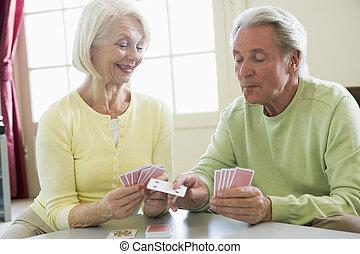 coppia, carte da gioco, in, soggiorno, sorridente