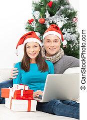 coppia, con, laptop., allegro, giovane coppia, in, cappello santa, seduta, chiudere, a, altro, e, computer usa
