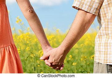 coppia, di, mani, tenendo stretto, in, uno, bello, campo giallo