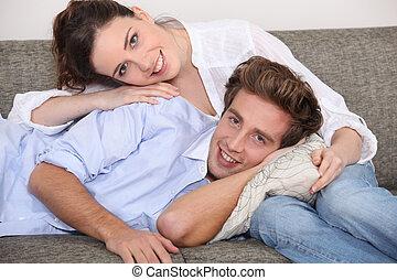 coppia felice, cuddling, su, divano