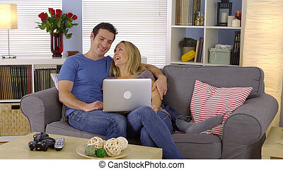 coppia felice, divano, laptop, seduta