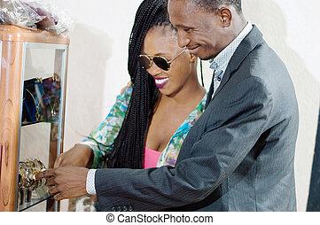 coppia felice, guardando, qualcosa, in, uno, storefront, di, uno, vendite, sto