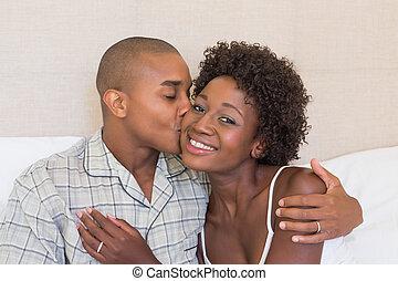 coppia felice, sedendo letto, cuddling
