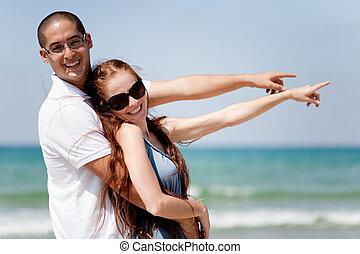 coppia, mare, indicare, sorridente