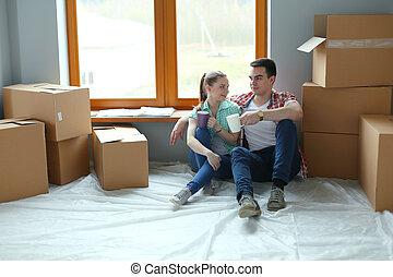 coppia, muoversi dentro, casa, sedere pavimento