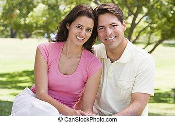 coppia, seduta, sorridente, fuori