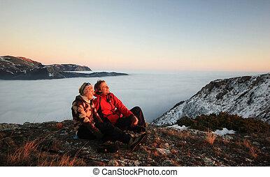 coppia, seduta, su, uno, montagna, a, tramonto, in, inverno