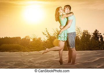 coppia, tramonto, abbraccia