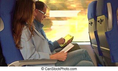 coppia, viaggiare, train., lettura ragazza, uno, libro, e, uomo, usando, suo, tavoletta, computer.