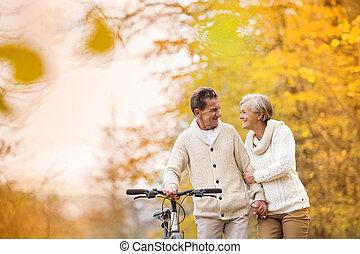 coppie maggiori, con, bicicletta, in, autunno, parco
