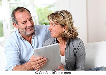 coppie maggiori, guardando, web pagi, su, elettronico,...