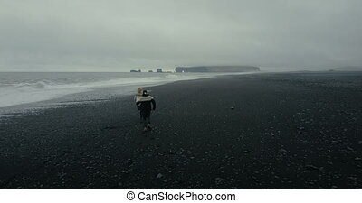 Copter flies after young couple running on the shore of the sea in icelandic sweater. Black volcanic beach in Iceland.