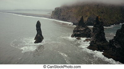 Copter flies away from the black volcanic beach and troll toes cliffs on the sea in Iceland. Beautiful landscape in fog.
