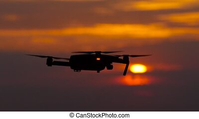 Copter flies, in the background a crimson sunset, he flies away