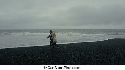 Copter flying near the young couple in icelandic sweater. Man and woman running on the black volcanic beach.